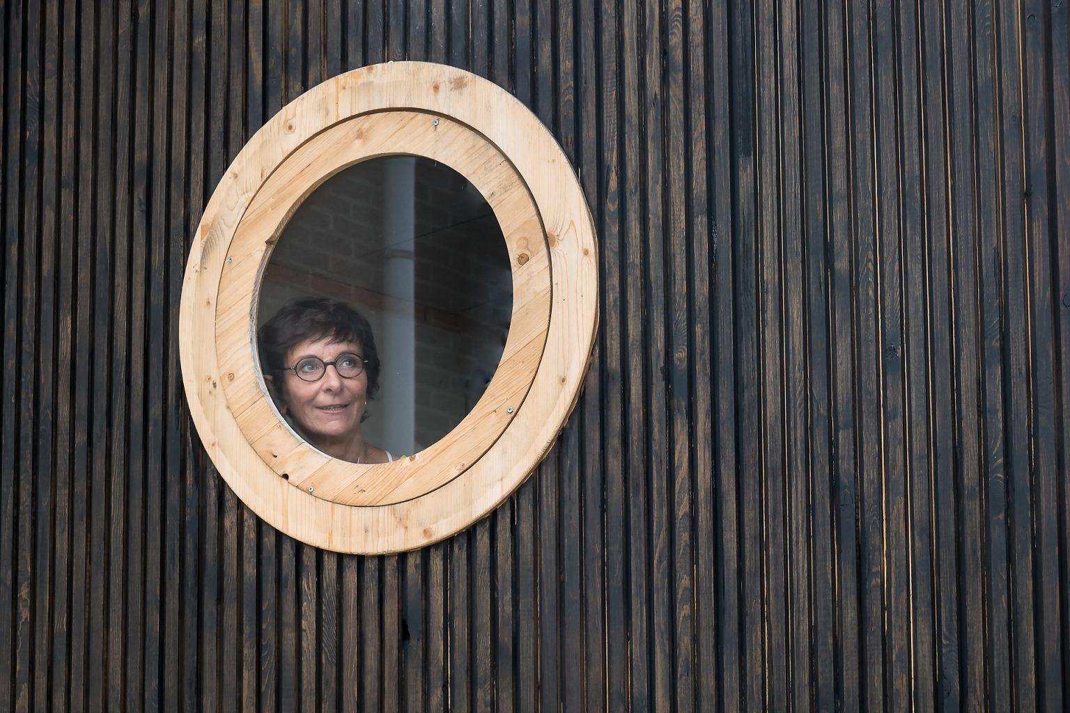 Portrait d'entrepreneur : Isabelle Dubois, architecte d'intérieur au hublot de sa roulotte en construction. Portrait en lumière naturelle et au plus proche de l'activité de l'entrepreneur
