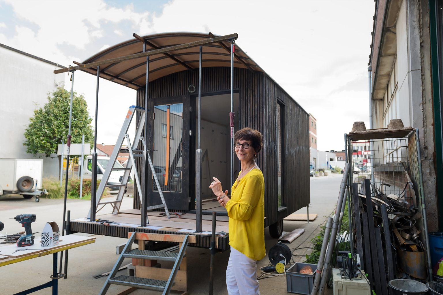 Portrait d'entrepreneur : Isabelle Dubois, architecte d'intérieuface à sa roulotte en construction. Portrait en lumière naturelle et suivi de l'activité de l'entrepreneur